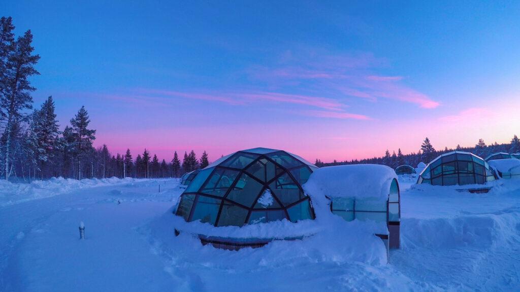 Glass igloo at Kakslauttanen Arctic Resort Finland during magical polar twilight.