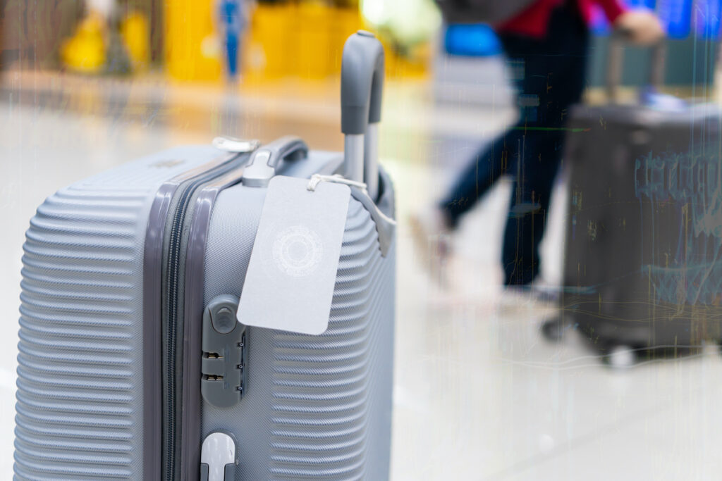 Luggage holder tag with blank label on silver suitcase.