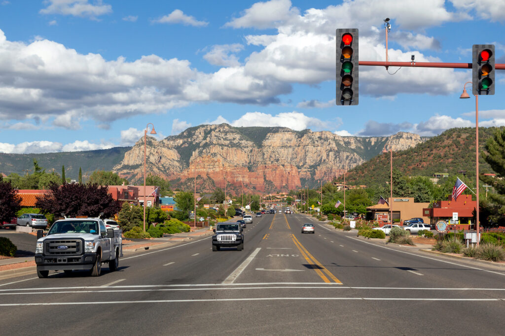 Main road in the city of Sedona, with some cars and the rocky mountains in the background.