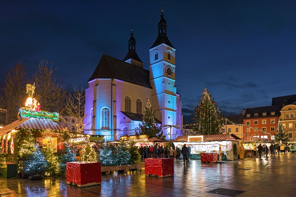 REGENSBURG, GERMANY - DECEMBER 13, 2019: The city's main Christmas market on the Neupfarrplatz (New Parish Square) around the Neupfarrkirche (New Parish Church) in dusk.