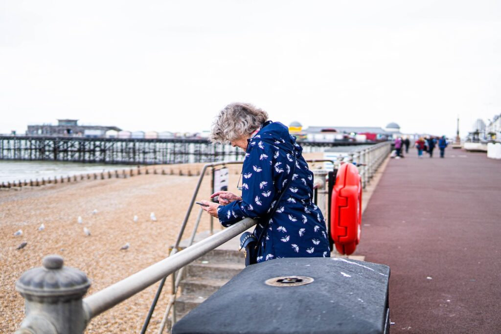 Senior woman with grey hair alone spending a day outside at the beach of England.