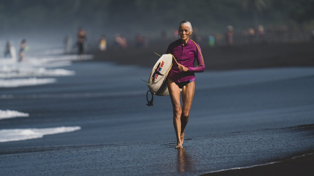 A 60 plus athletic, fit woman with gray hair is cheerfully walking down the beach carrying a surfboard.
