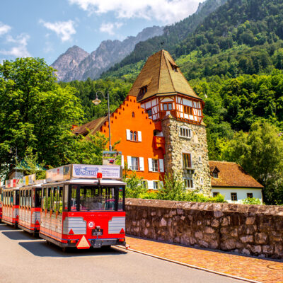 People on the tourist train visit famous red house with wineyard in Vaduz city.