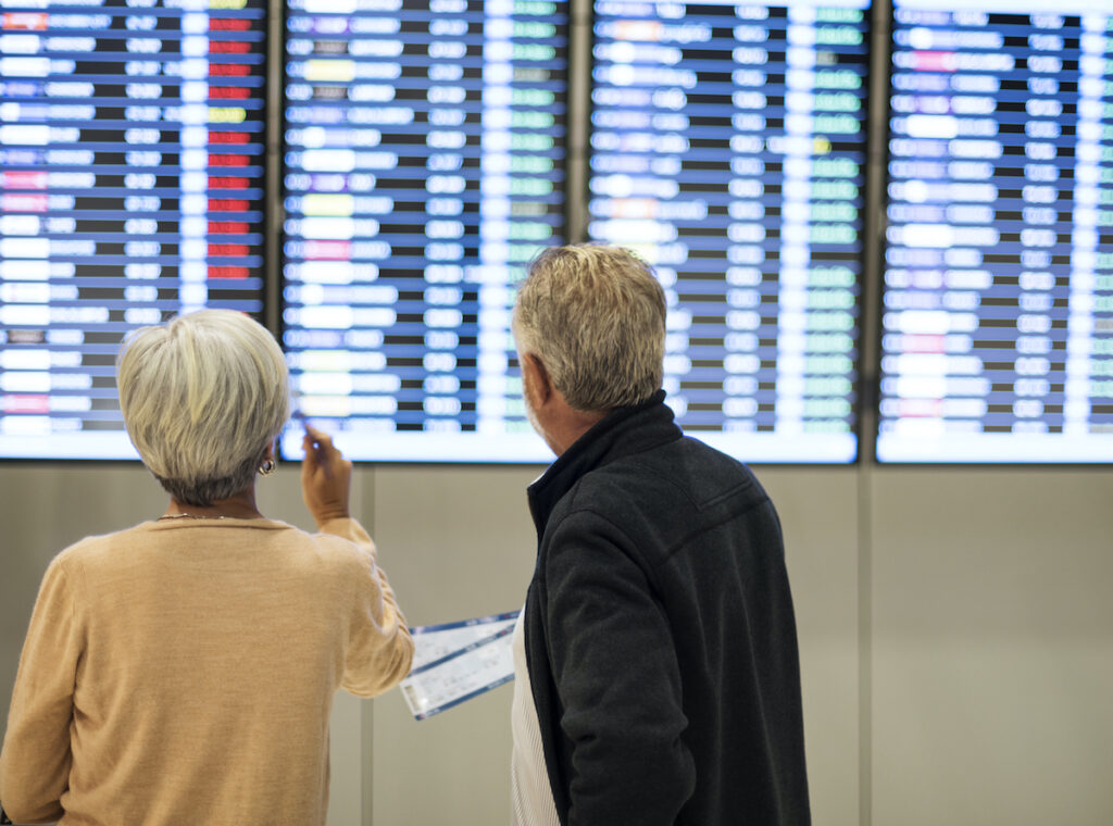 Senior couple traveling in airport scene, looking at flight times.
