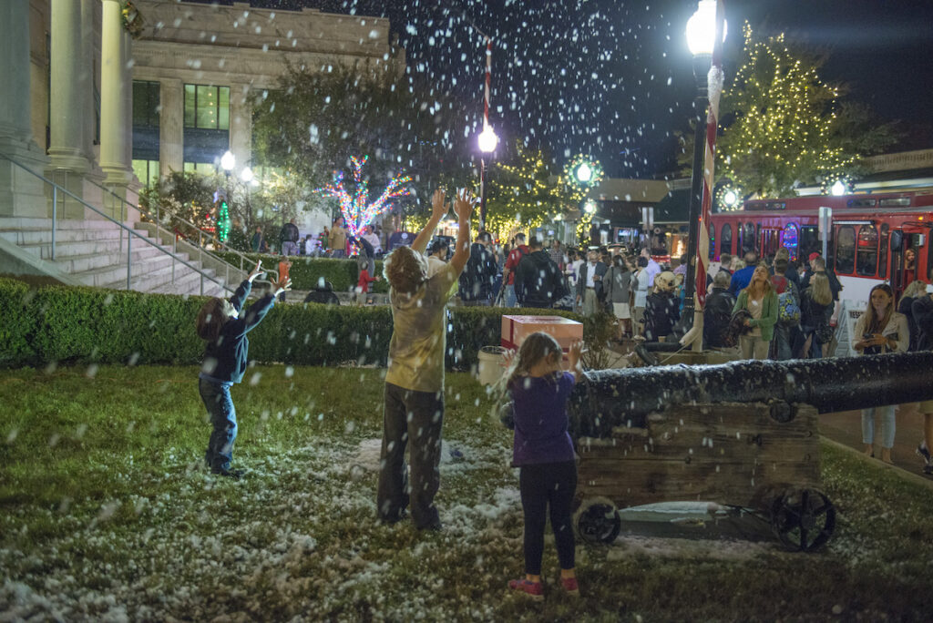 Happy children play in the falling snow at Winterfest in Pensacola.